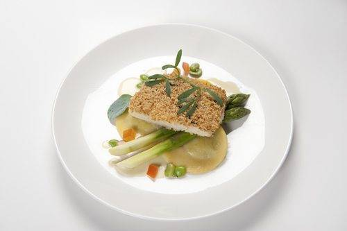 Fillet of halibut with a truffled herb crust, sea herbs, asparagus, crushed broad beans and pumpkin ravioli, with a champagne beurre blanc