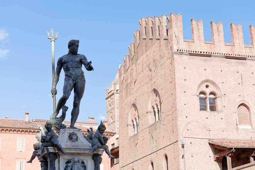 Vvoe - sculpture of Fountain of Neptune on Piazza del Nettuno and Re Enzo palace in Bologna in sunny day, Italy