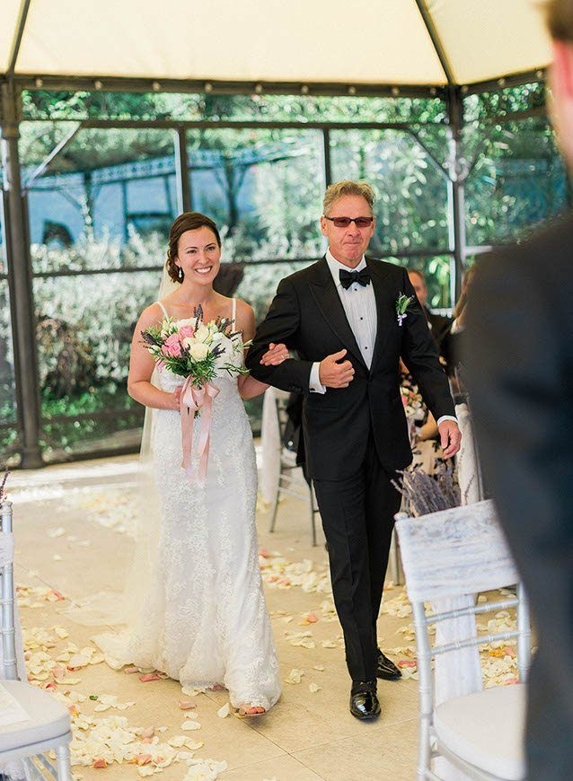 Here she comes! Escorted on a proud, supportive arm, Jodi's radiant happiness is clear as she makes her way towards her groom.