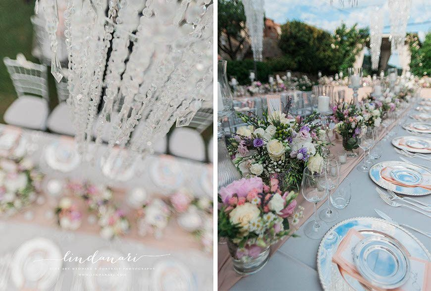 Sparkling crystal chandeliers hung over elegantly draped tables, with pink silk runners and silver chargers. Tea lights in small glasses sparkled along with a host of larger candles and more vases of beautiful flowers.