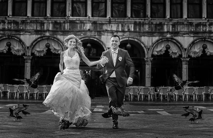 bride groom running on san marco square venice italy - Luxury Wedding Gallery