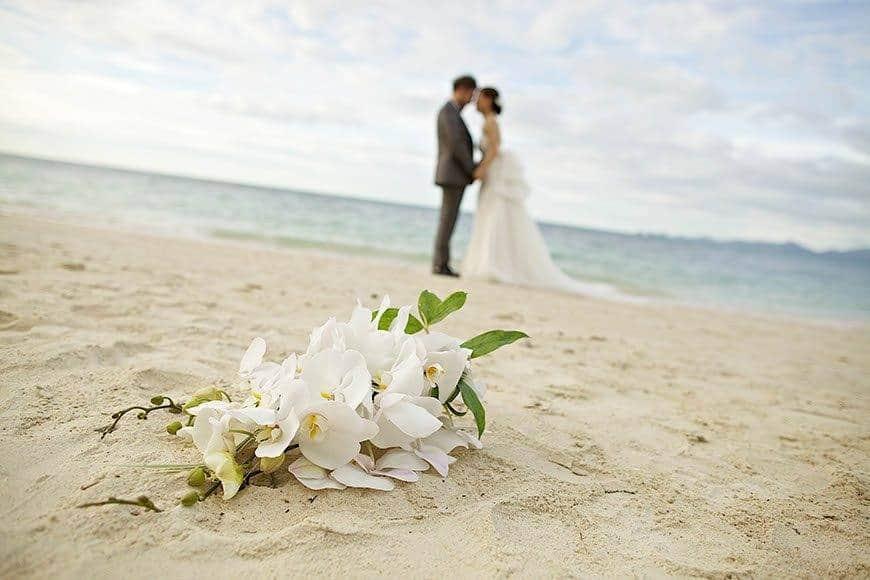 Pearl Island Bahamas wedding beach couple flowers - Luxury Wedding Gallery