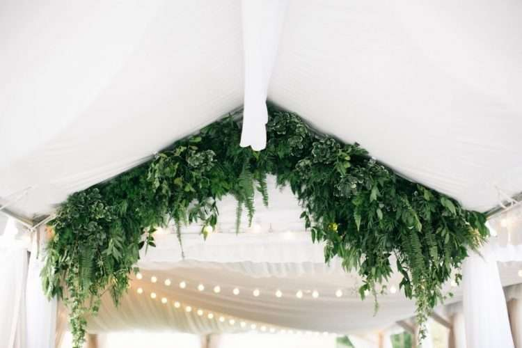 A lush green foliage arch makes a striking entrance. Pair with spotlights or twinkling fairy lights for a magical wedding wonderland. Photo: Lisa Foster Floral Design