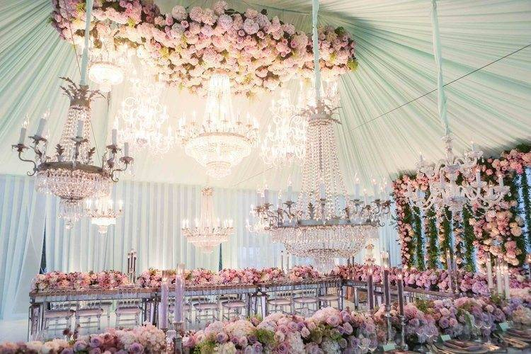 A gorgeous combination of sparkling chandeliers and abundant florals Photo: White Lilac Inc