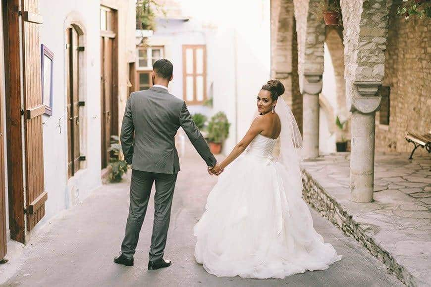 Bride and Groom walking down a cypriot village road - Luxury Wedding Gallery
