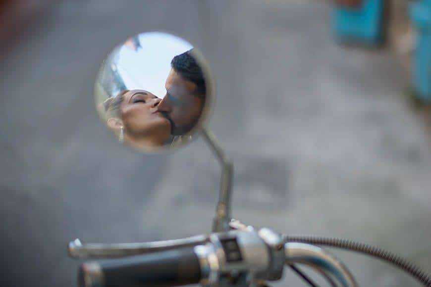 Bride and groom kissing in mirror of old Italian scooter in Cyprus - Luxury Wedding Gallery