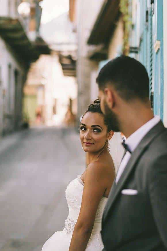Bride and groom looking at eachother in a village in Cyprus - Luxury Wedding Gallery