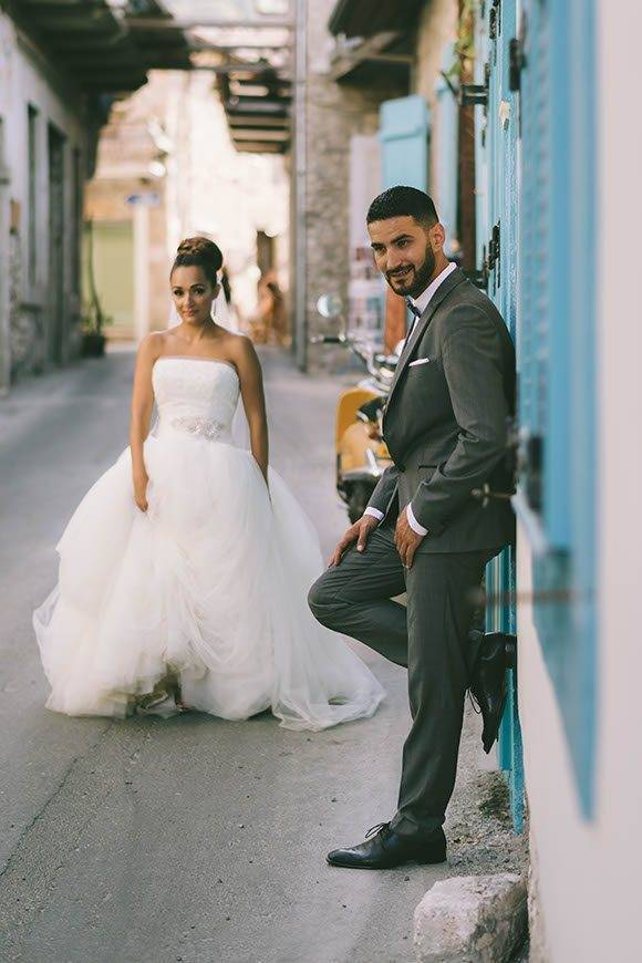 Bride and groom standing in a little alley in a village in Cyprus - Luxury Wedding Gallery