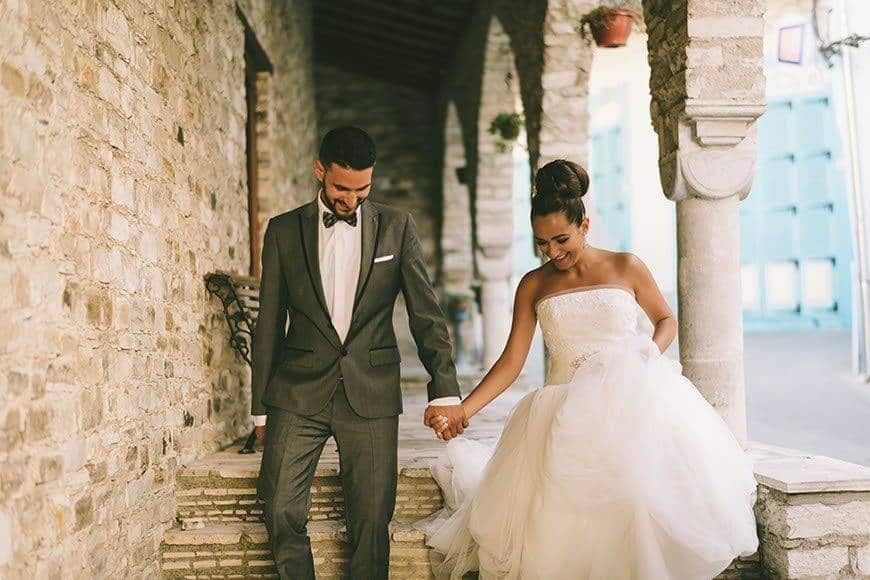 Bride and groom walking down an alley in a village in Cyprus - Luxury Wedding Gallery