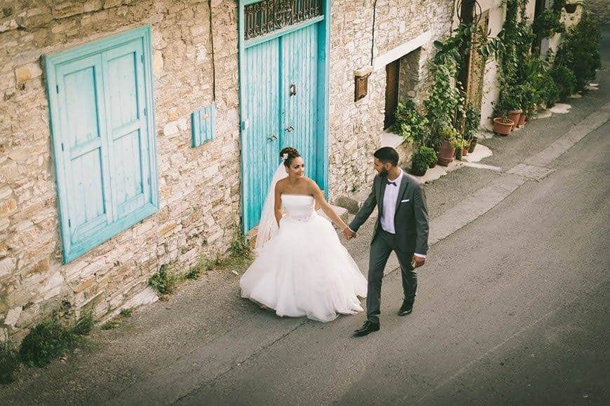 Bride and groom walking on a road in a small cypriot village - Luxury Wedding Gallery