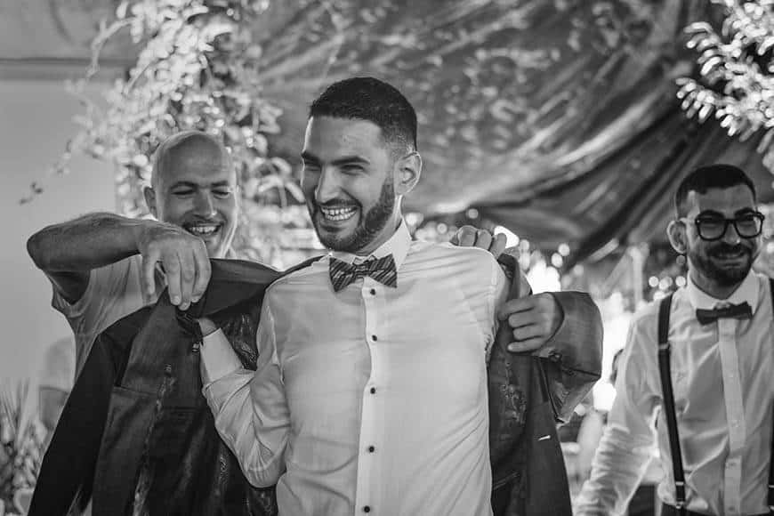 Father puts on jacket of groom with best man - Luxury Wedding Gallery