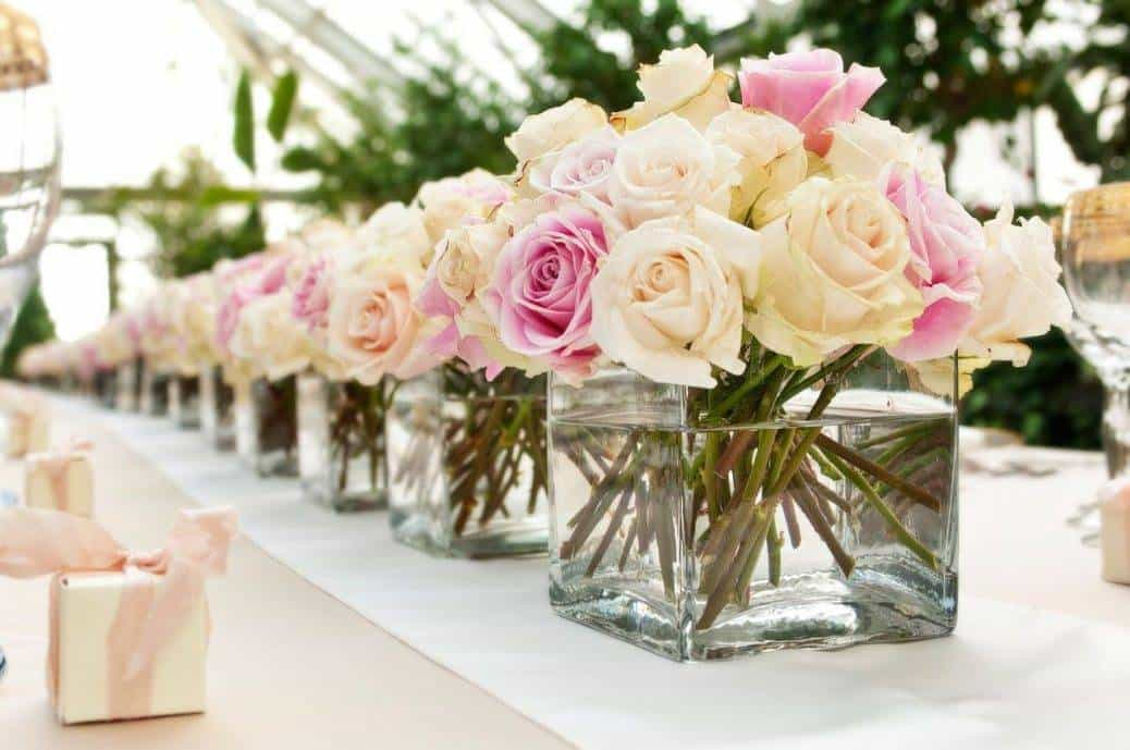 Simple and classic, just display as many vases of roses as you can in your chosen colour palette. Then let guests take them home! Image: Quartz Weddings & Events