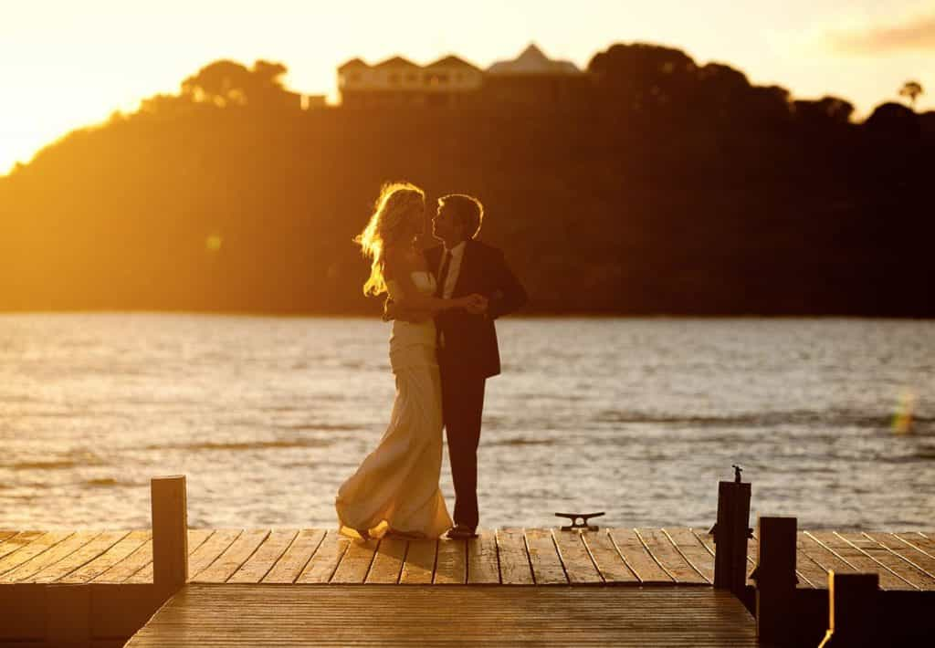 couple standing on jetty - sunset-compressed